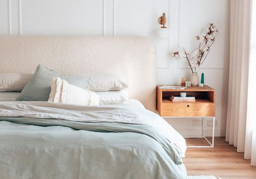 Soft pink pastel bedroom with wooden nightstand.