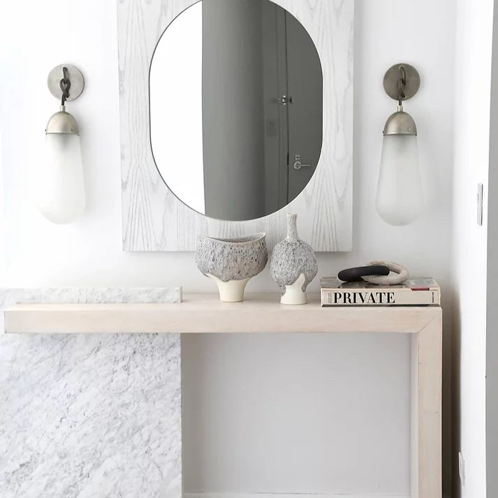 Modern marble entryway mirror and light wooden table.