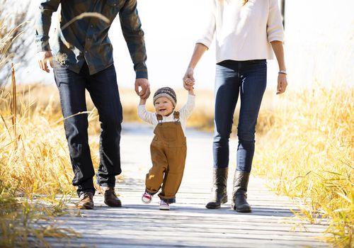 bebé cogidos de la mano con los padres