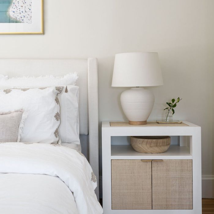 mostly white minimalist bedroom, white lamp and small lamp on bedside table,