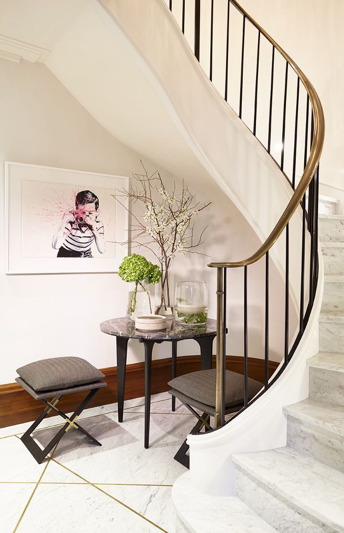A café table and framed art featured in entryway with curved staircase