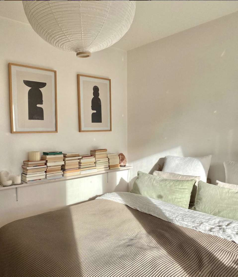 bedroom with long floating shelf filled with books