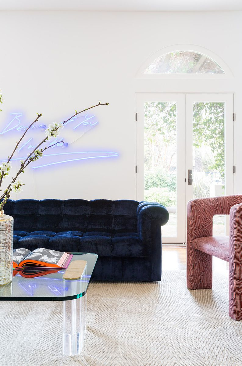 Chic living room with blue velvet sofa, pink chair, and a neon sign.