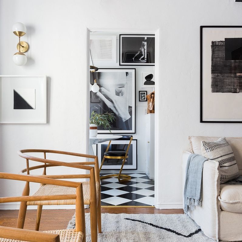 Apartment living room with a view into the kitchen's floor-to-ceiling gallery wall