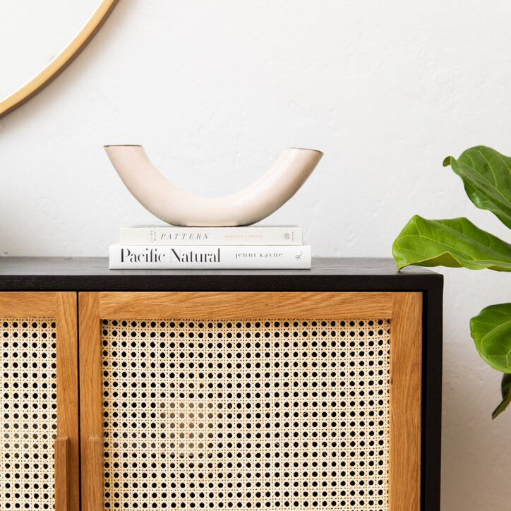 A console table with a small ivory sculpture on it