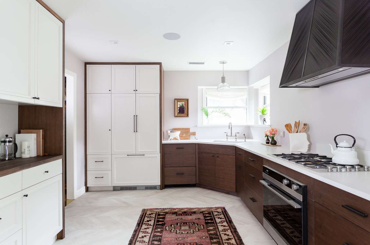 A kitchen with wood cabinets and a dark red printed rug