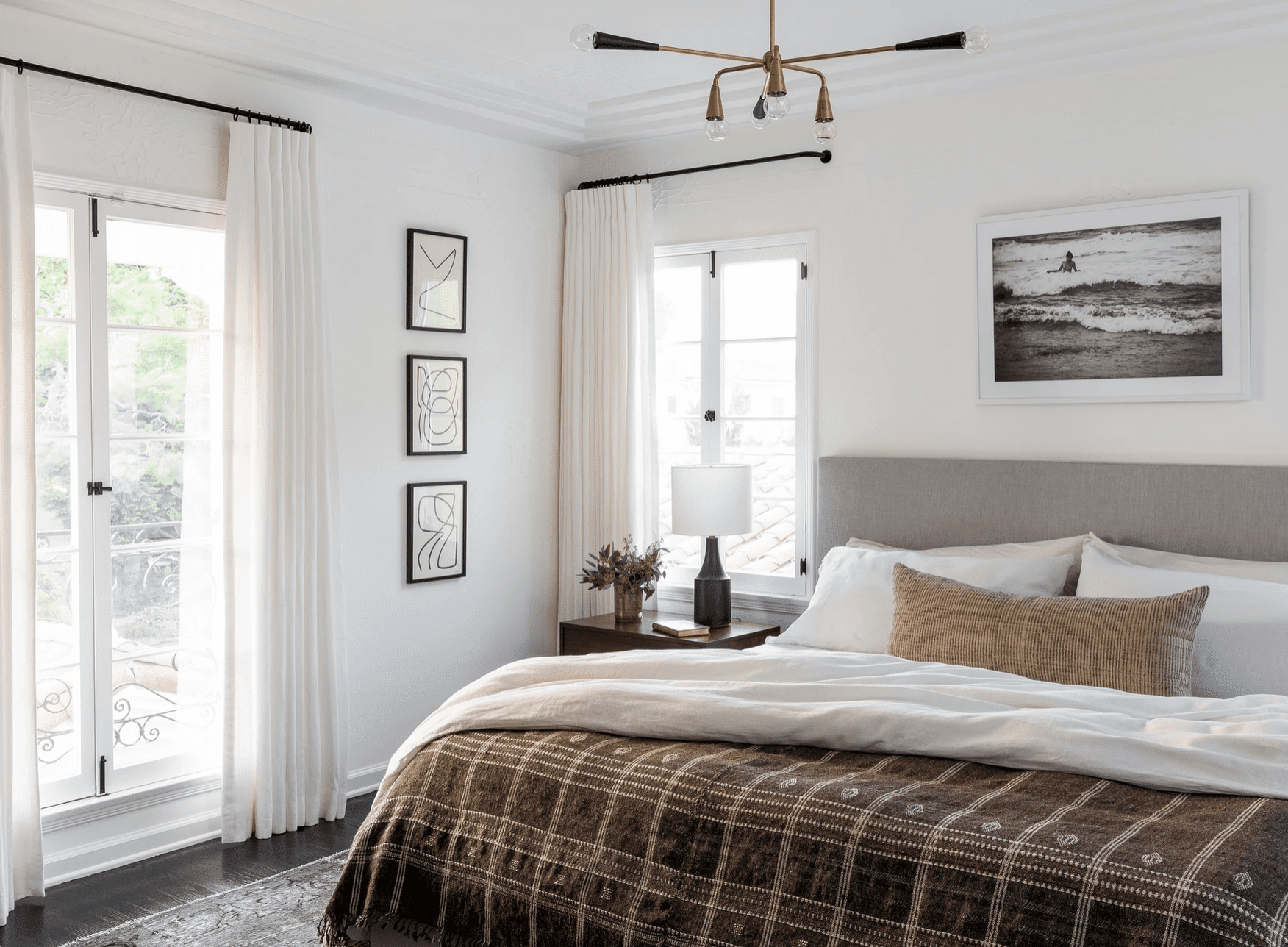 A bedroom with a geometric chandelier and a more classic table lamp