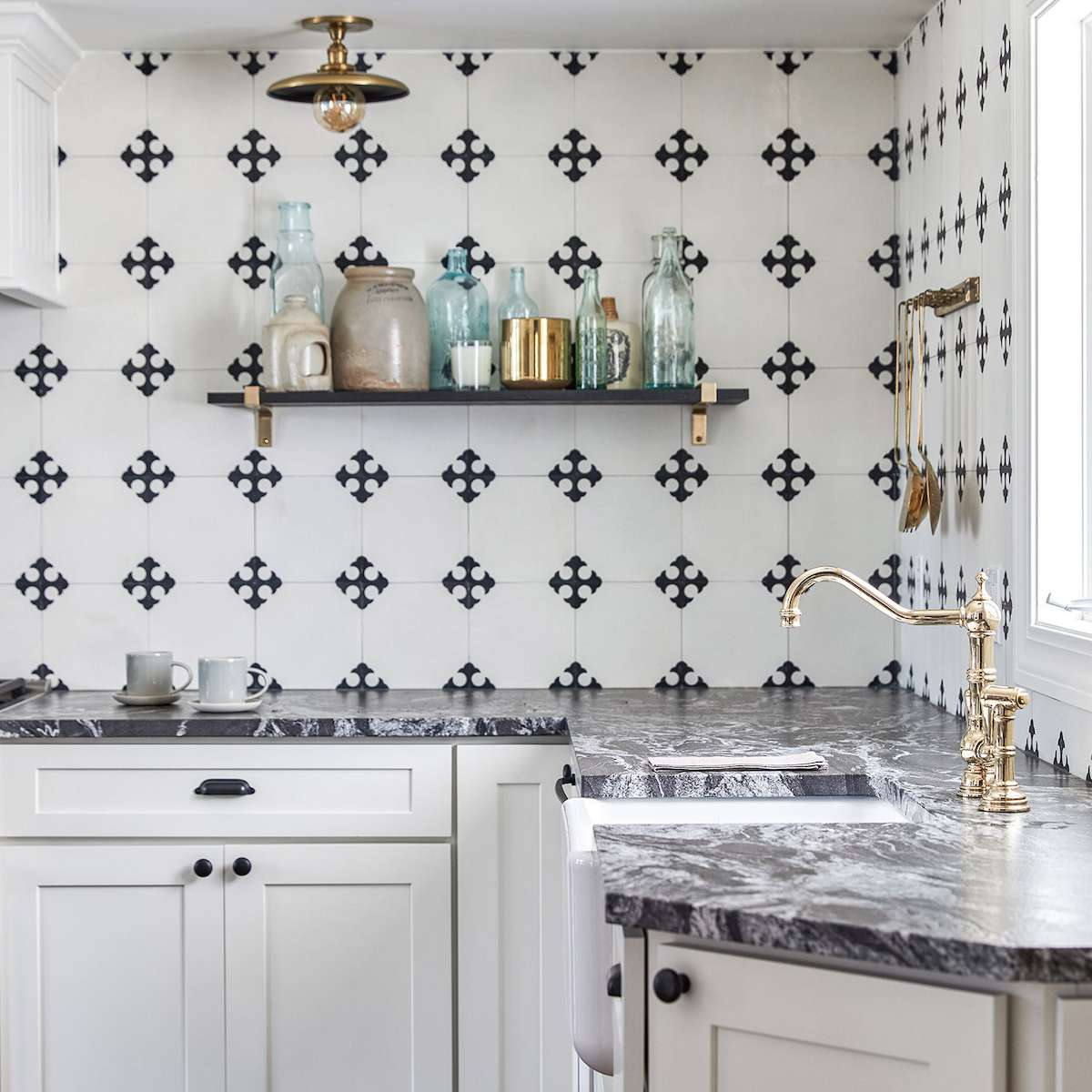 A kitchen with a bold tiled backsplash and striking marble countertops