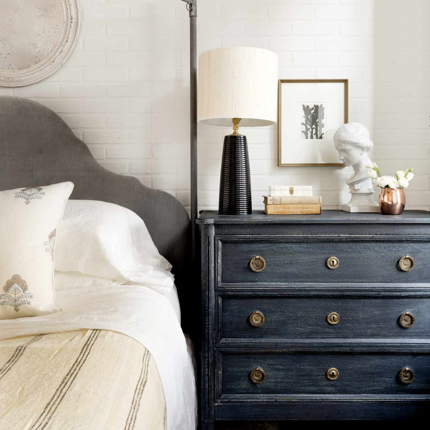 A bedroom with a canopy bed and an antique dresser as a nightstand