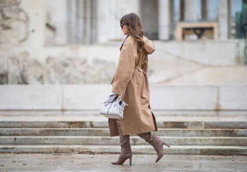 una mujer en una gabardina caminando por una acera