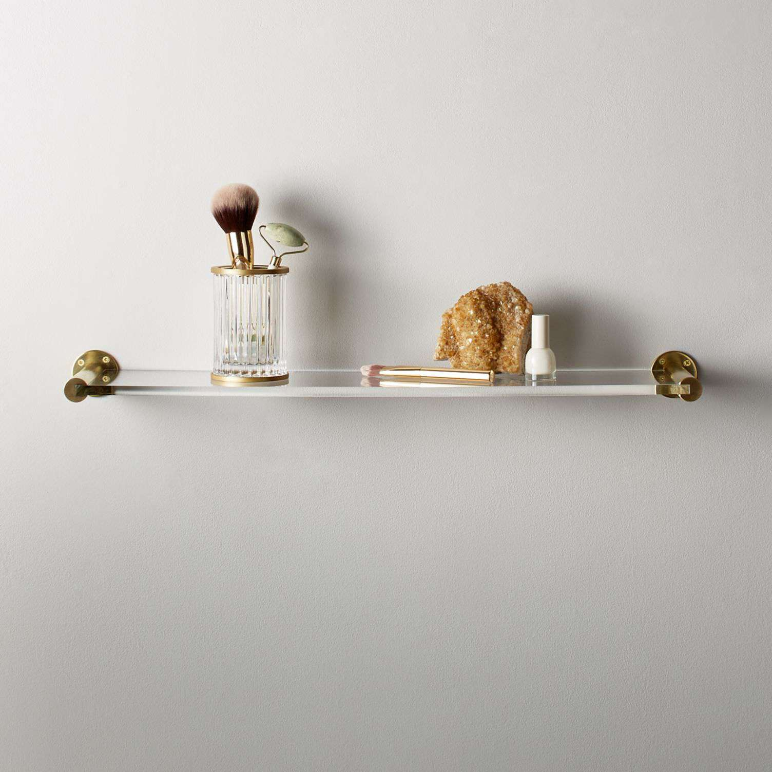 A brass-and-acrylic wall shelf with bathroom accessories on top.