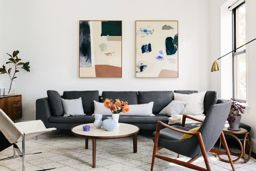 A midcentury modern-inspired living area featuring furniture with tailored upholstery.