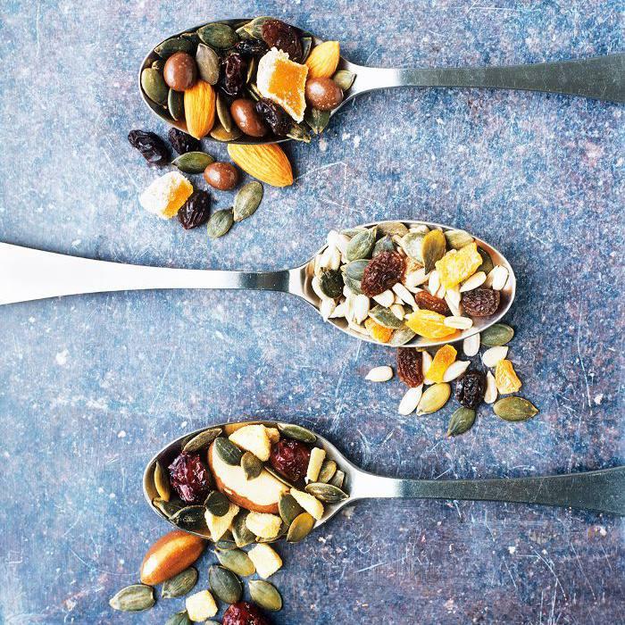 cucharas llenas de una mezcla de frutas y nueces