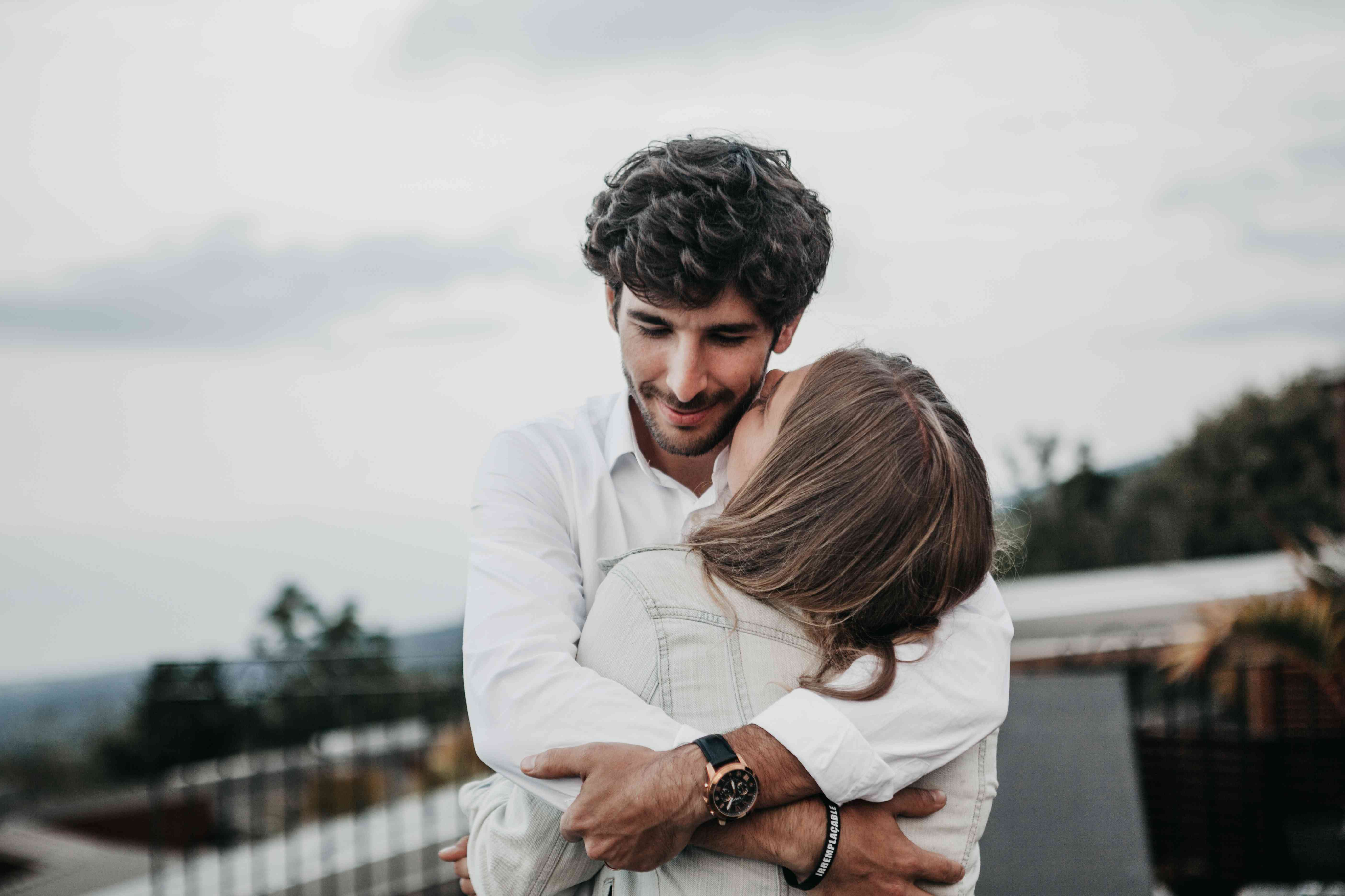 Hombre más joven abrazando a una mujer