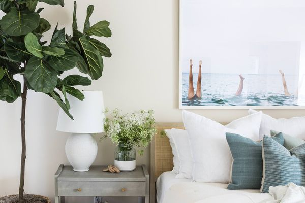 A bedroom filled with white, beige, and blue modern coastal decor