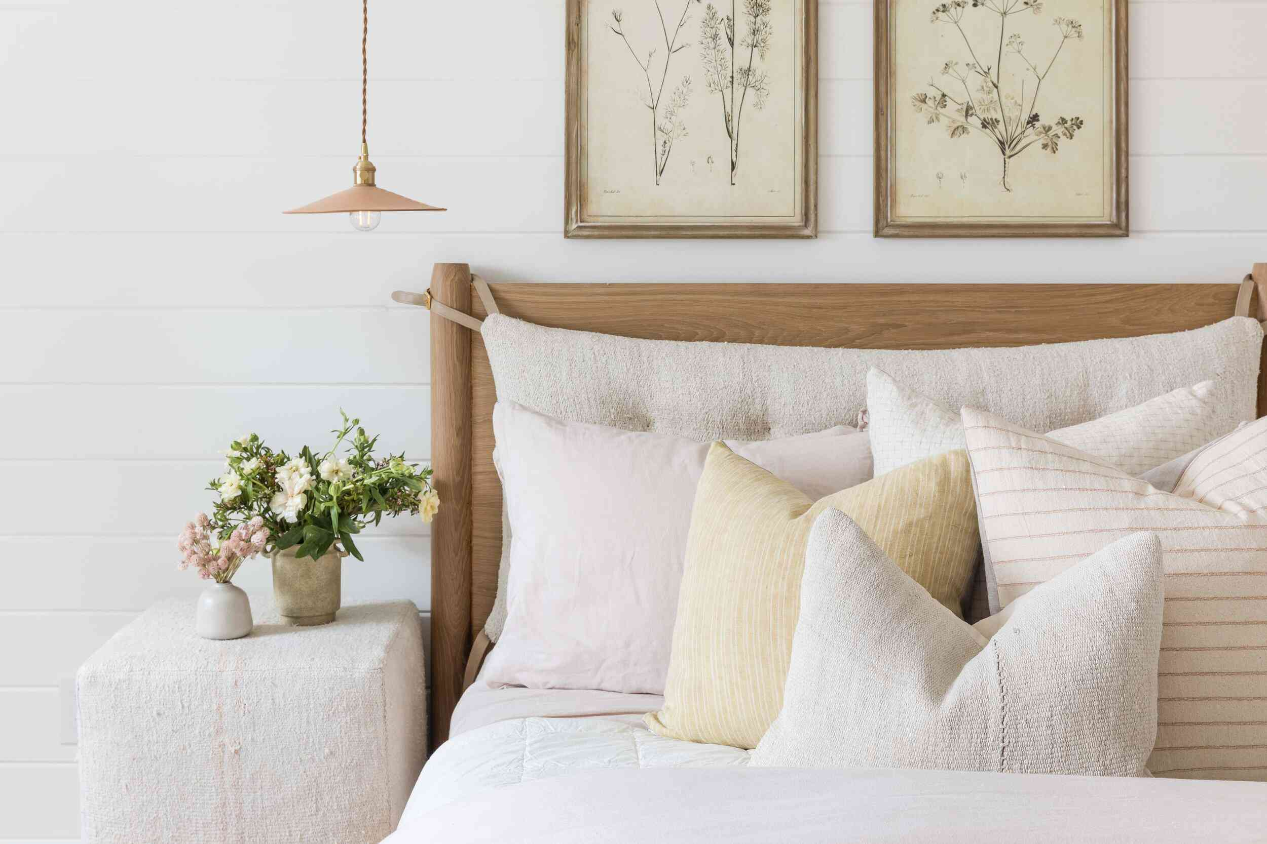 A mostly off-white bedroom with a washed-out lavender pillow