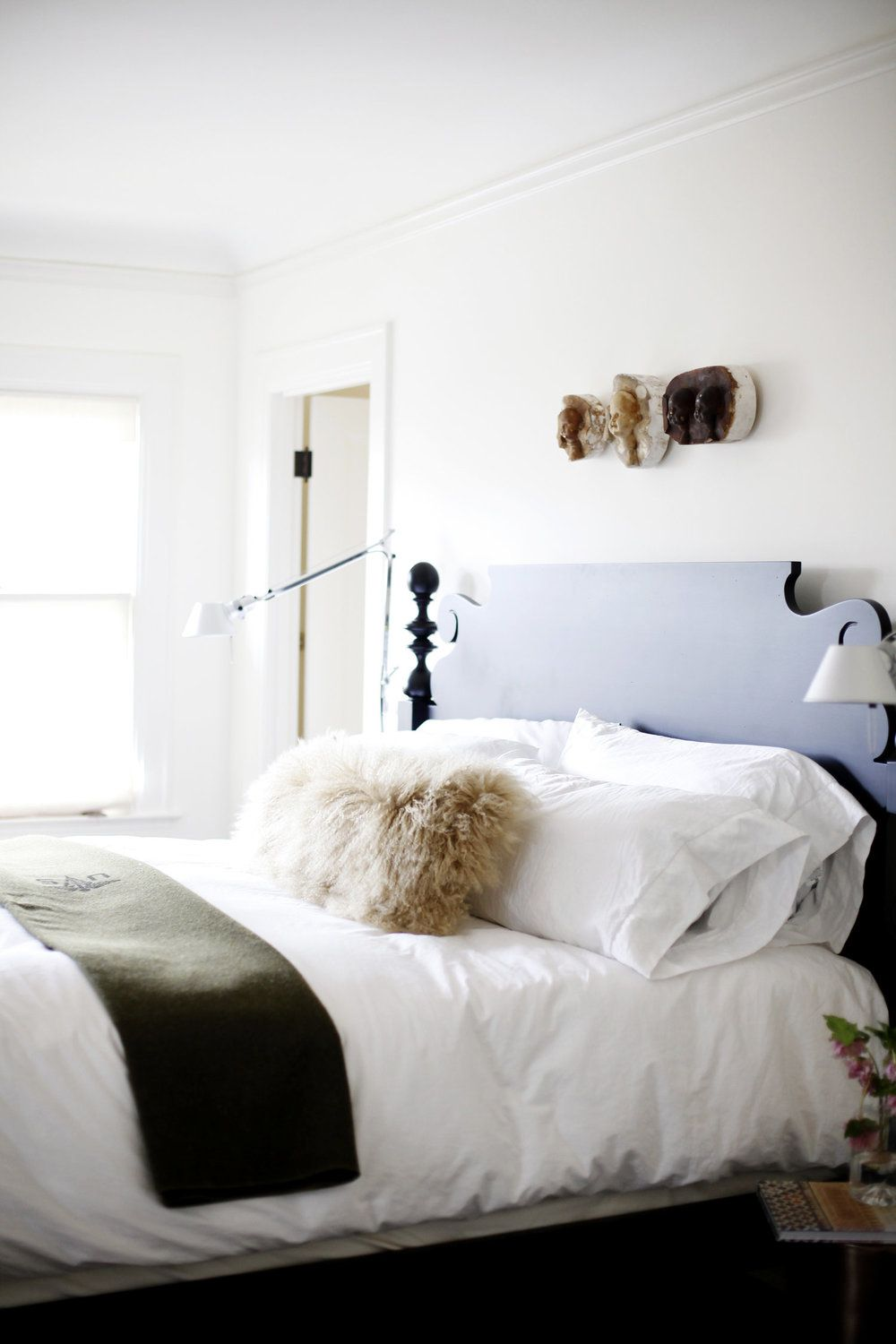 A white bed on a solid bedframe