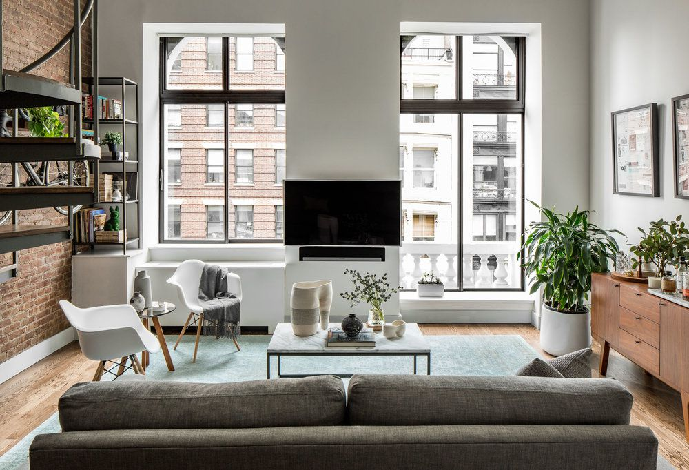 A loft apartment in Manhattan's NoHo neighborhood with 2 large floor-to-ceiling windows and an exposed brick wall.