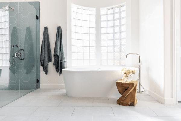 White tile bathroom with blue tile shower.
