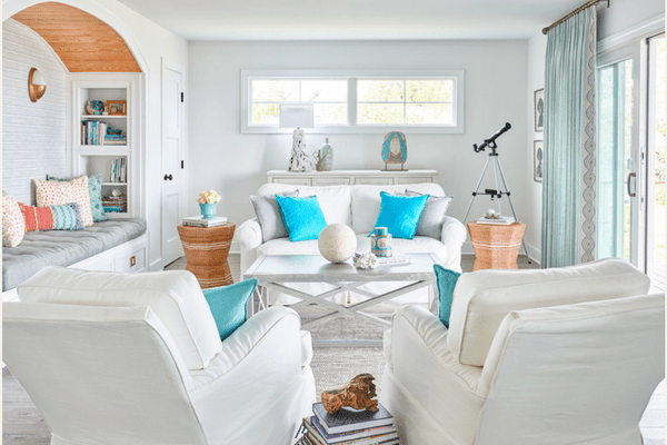Coastal living room with white sofa and armchairs.