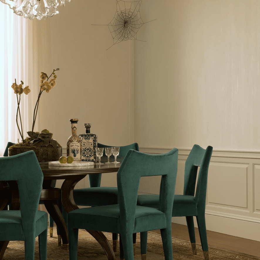 A circular dining room table surrounded by teal upholstered chairs