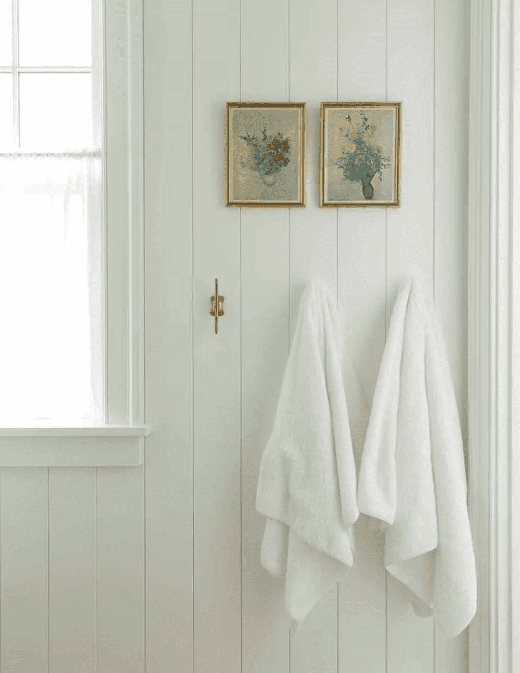 A bathroom decorated with two small paintings