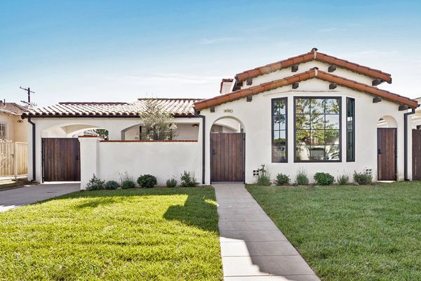 Spanish style home with white stucco and brown roof.