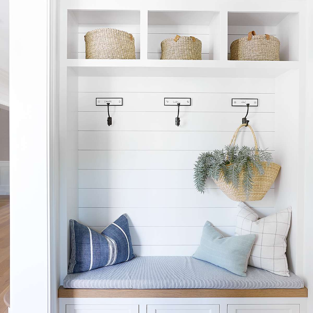 An all-white mudroom lined with hangers, drawers, and cubbies