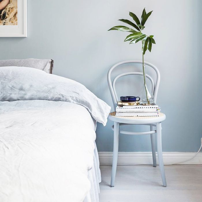 a bedroom with a chair as a nightstand