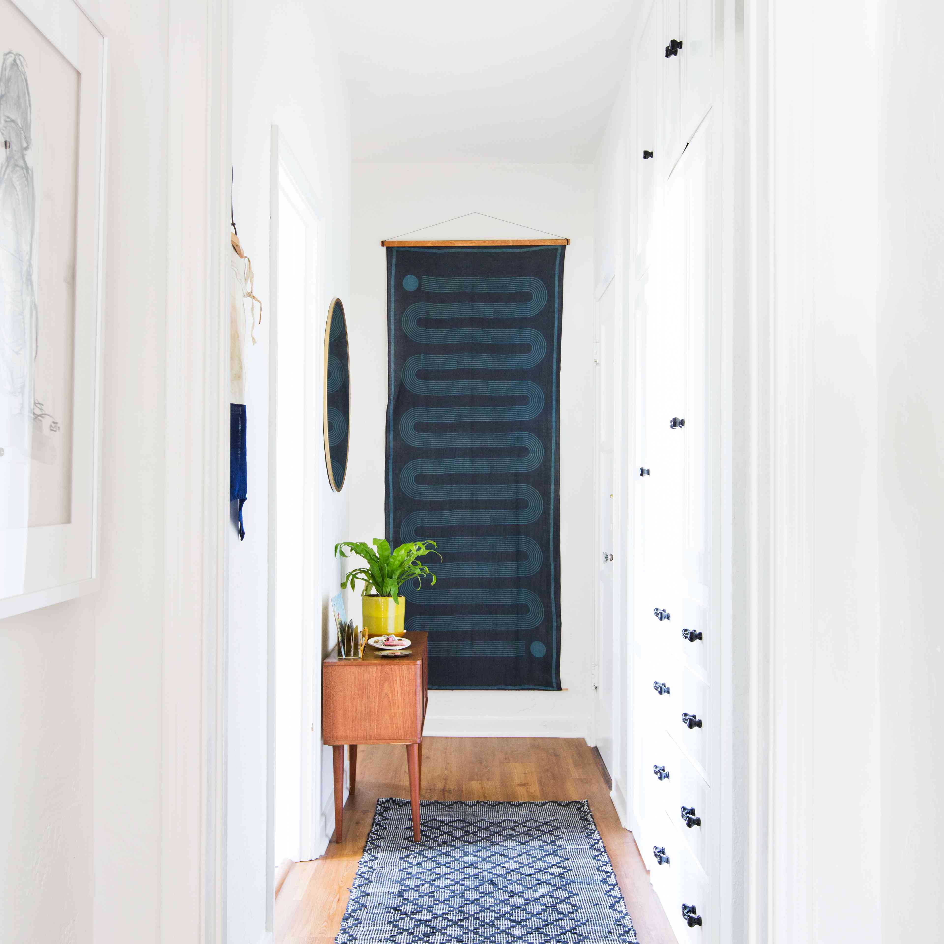 Apartment hallway with rug and woven hanging