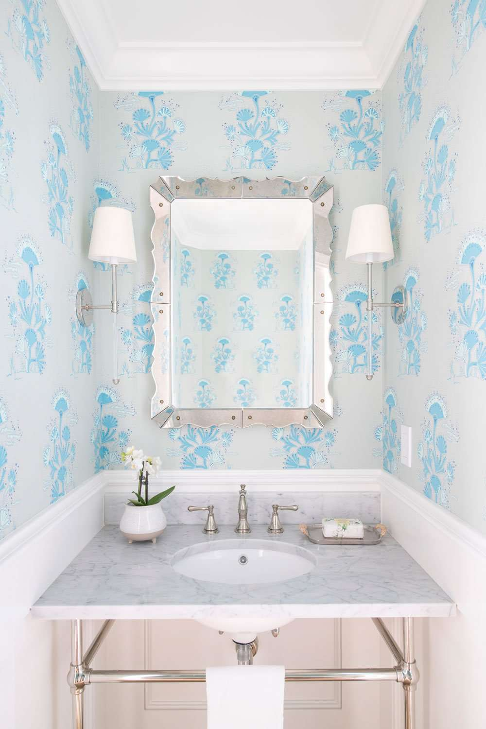 Bathroom with light blue floral wallpaper.