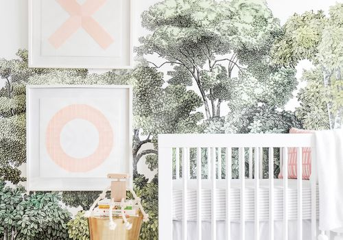 nursery with tree wallpaper and light pink art print accents