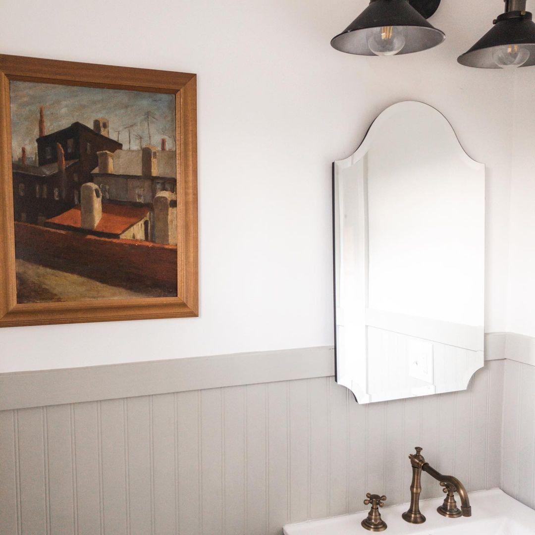 Beadboard bathroom with vintage art.