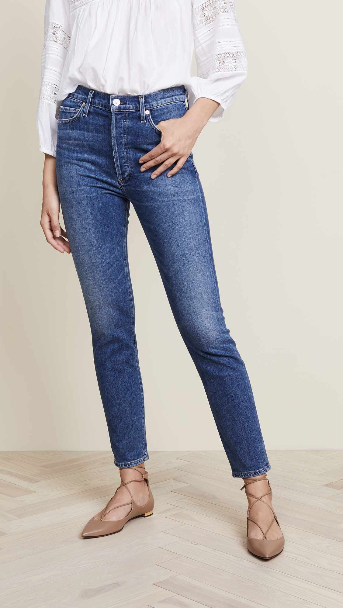 A woman modeling a pair of slim fit, ankle length jeans.