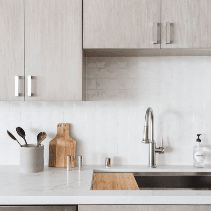 A kitchen with ash gray wood cabinets and a backsplash lined with shiny white tiles