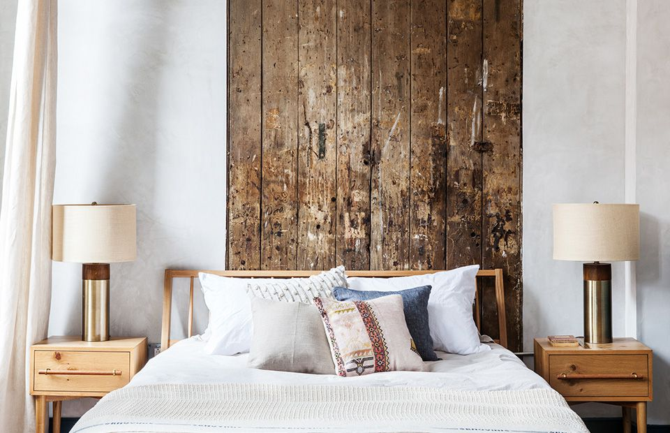 A bed in a wood-paneled bedroom