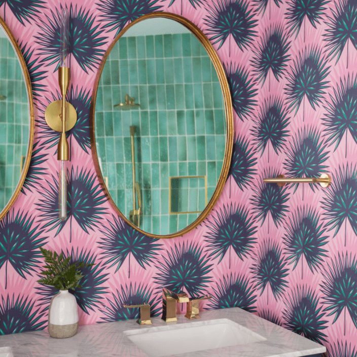 A powder room lined with bold pink printed wallpaper