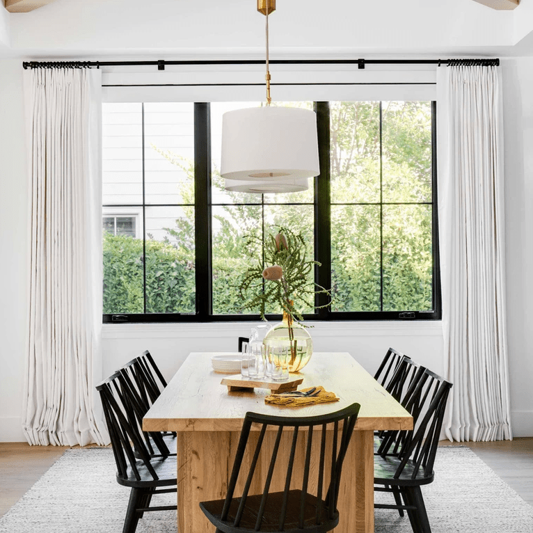 A wooden dining room table with a large yellow vase on it
