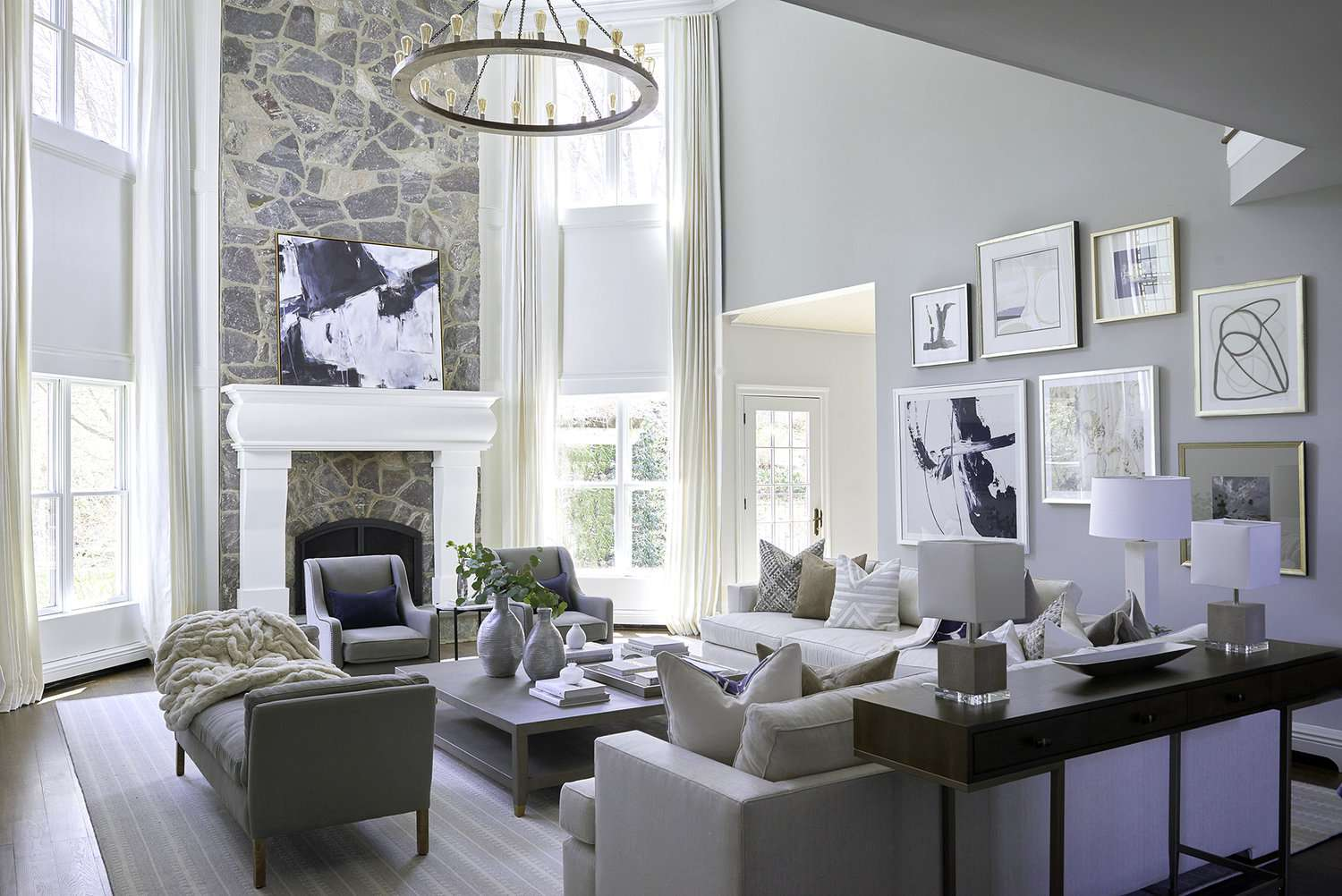 White rustic living room with tall ceilings and chandelier.