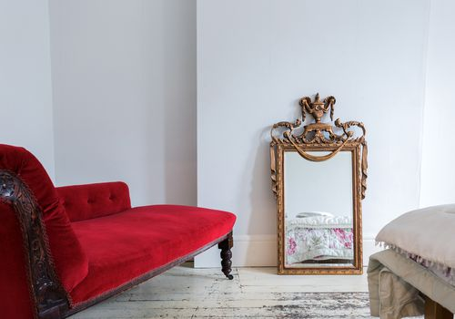 Red fainting couch with gold mirror