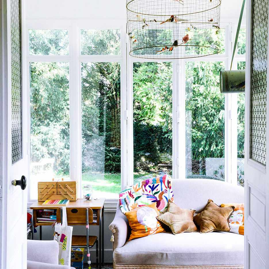 Sunroom with ornate vintage couch and birdcage.