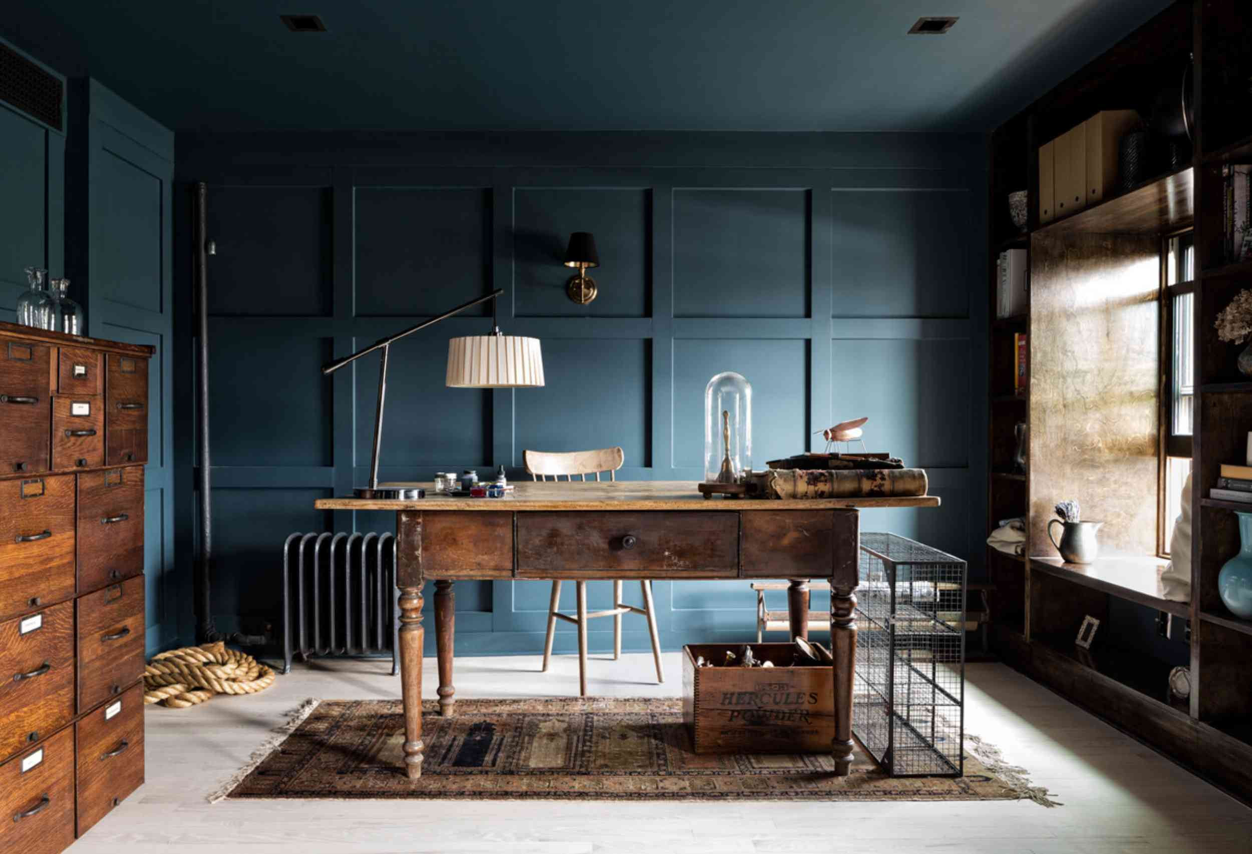 Dark navy office with wall paneling and vintage furniture
