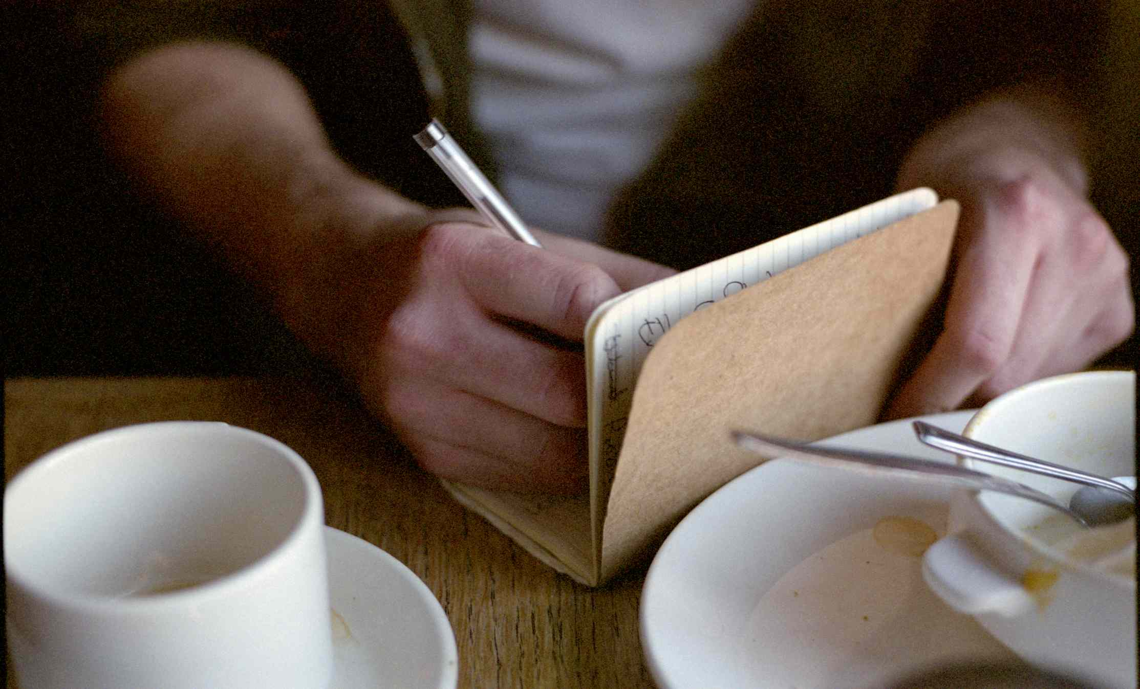 Hands writing in notebook, surrounded by empty coffee cup