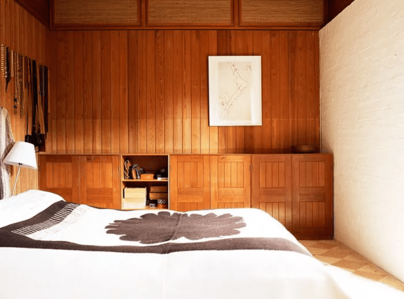 Dim lighting and wood paneled walls in a sparsely decorated bedroom