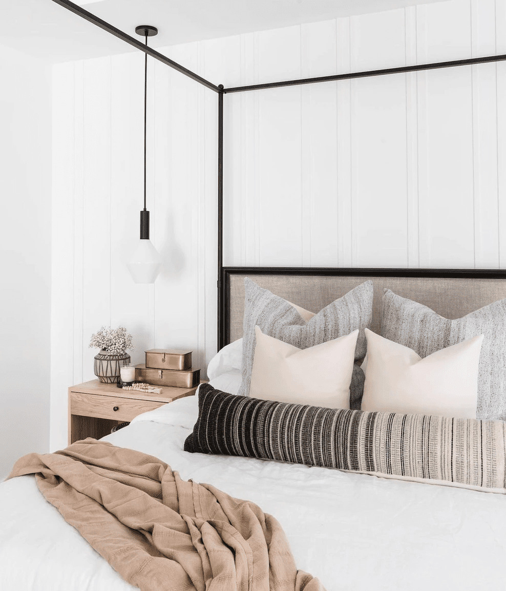 A bedroom with a black canopy bed frame and a matching light fixture