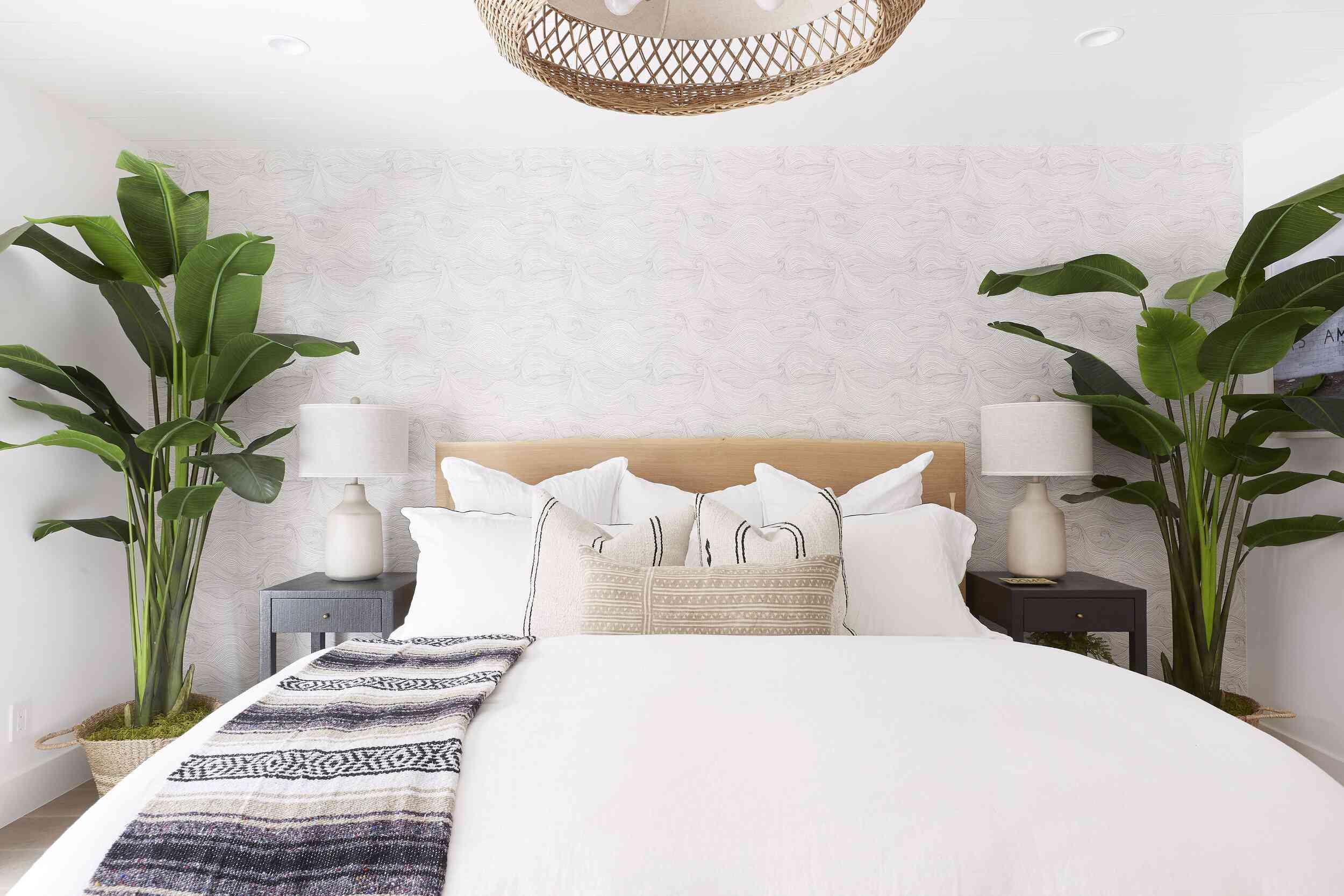 Light beige wallpaper behind coastal bed.