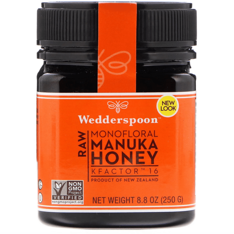 A black jar of manuka honey with an orange label.