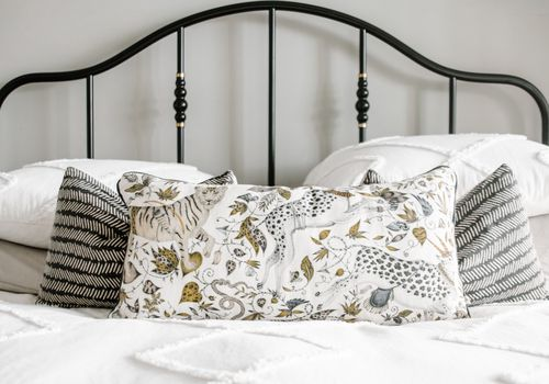 White bedspread with custom leopard throw pillow.