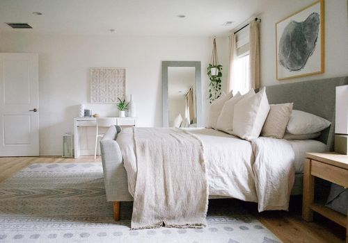 Peaceful shot of bedroom with neutral bed linens.