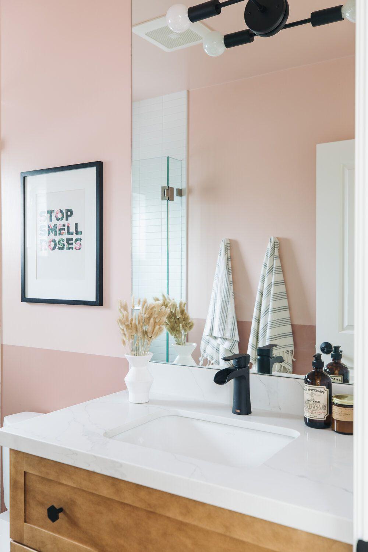 Modern bathroom with pink walls, framed typographic art piece